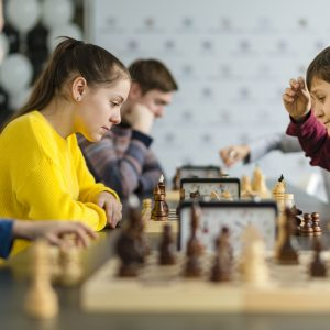 Kids of different ages, boys and girls, playing chess on the tournament in the chess club