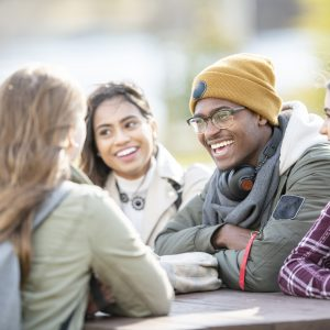 Five young adults are sitting at a picnic table outside on a fall day. They are smiling and chatting.