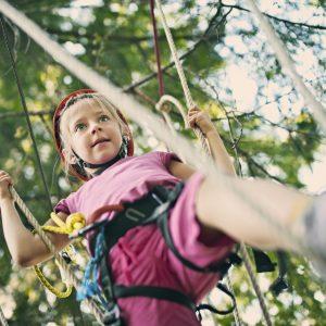 """Little girl wearing a helmet, walking on lines in the outdoors adventure park."""