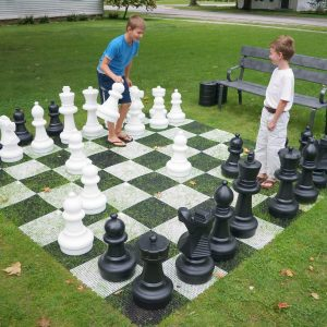 Young boys playing lawn chess.