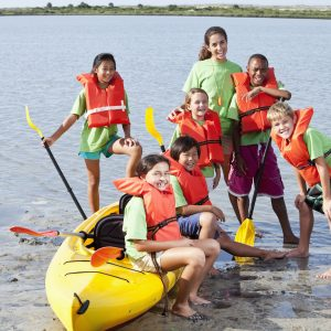 Teenage girl and group of children with kayak at water sports camp.