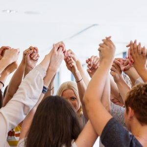 Group of women standing toghether in the circle and holding raised hands. Unity concept.