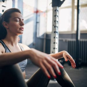 One beautiful fit young woman sitting on the floor in the gym, resting after training.