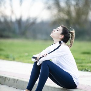 EXHAUSTED YOUNG WOMAN HAVING A REST AFTER HER EXERCISE ROUTINE SITTING ON THE SIDEWALK WITH A BLURRY BACKGROUND OF TREES